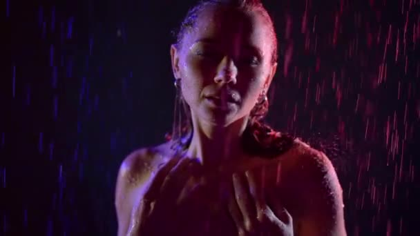 water drops are falling on head and naked shoulder of amazing beautiful woman, standing in dark