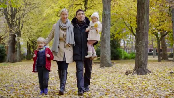 Beautiful family of four spending day together walking in autumn park, beautiful yellow scene outdoor.