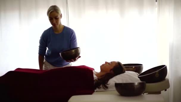 Frau auf einer Klangtherapie im Wellnessbereich. Massagetherapeutin mit tibetischer Klangschale, meditative Klangmassage. Seelenbehandlung.