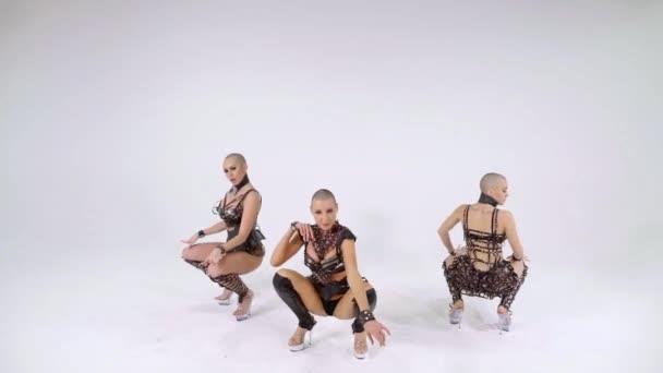 Tři štíhlé sexy holohlavý dívky tančí smyslný tanec striptýz v kožených oděvů na bílém pozadí izolované
