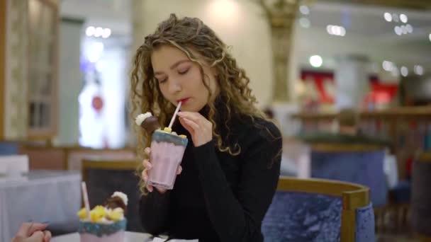 hezká mladá žena je popíjení chutný koktejl se šlehačkou a zmrzlinou, posezení v kavárně