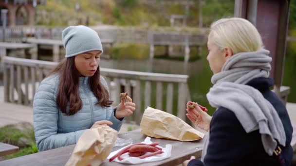 Dva nejlepší přátelé sedí u café tabulka venkovních a jíst klobásy, ženy s vážnou konverzaci