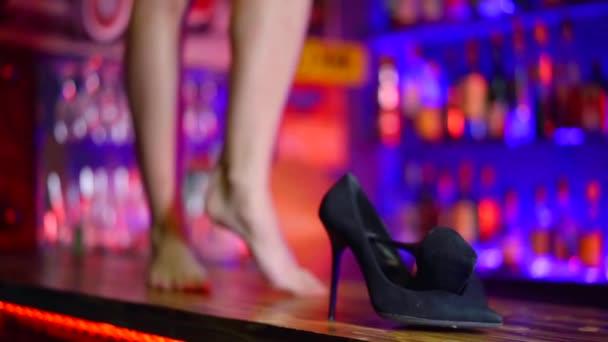 Nahaufnahme. Frauen schwarze Schuhe und Füße an der Bar. Betrunkene Frau tanzt auf dem Tisch