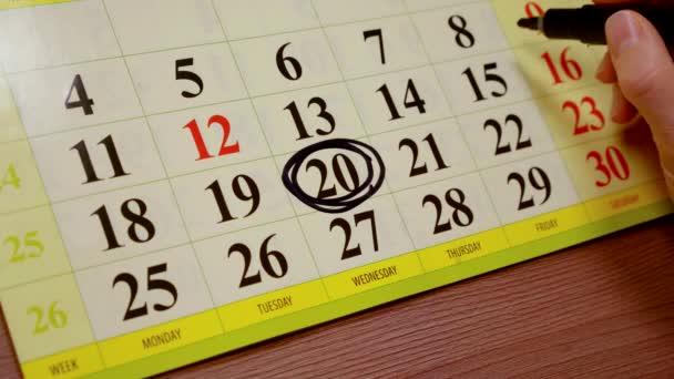 žena dělá značky poznámky v kalendáři. měsíční plánování