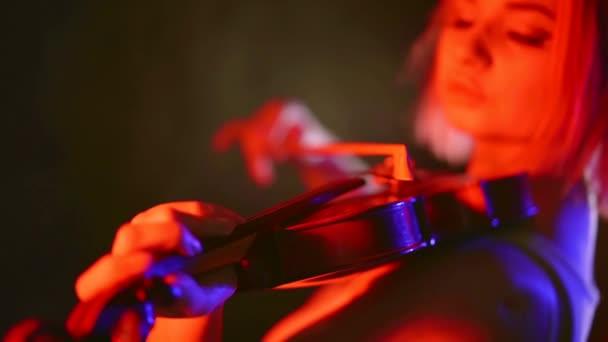 A fiatal, vonzó modell lány játék hegedű fedett stúdió, a lány rózsaszín fényt közeli lövés.