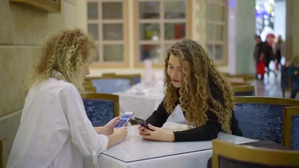 Dvě krásné kamarádky posezení v kavárně s chytrými telefony a mluví o online fotografie
