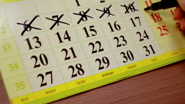 zblízka. ženská ruka značka v kalendáři křížů z posledních dnů v týdnu a plány činností pro zbývající data