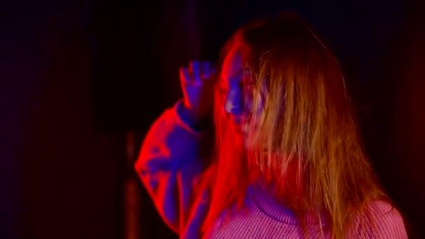donna in luce al neon, bellissima modella ragazza in rosa maglione lavorato a maglia. Danzatore della discoteca dancing nella luce Uv