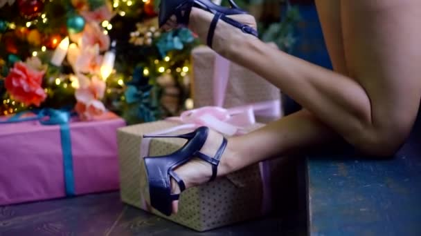 detail view on legs of woman shod in black shoes with high heels in room with Christmas decorations