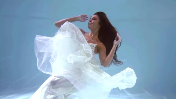 atemberaubende Königin Mädchen in einem langen weißen Kleid posiert unter dem Wasser schwimmend, kristallblaues Wasser.