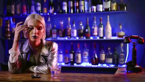 mladý roztomilý homosexuální muž s bílými vlasy sedí v baru za barem a silného alkoholu