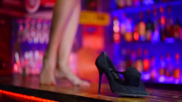 Frau tanzt auf einem Bartresen in einem Nachtclub, Nahaufnahme ihrer nackten Beine und Schuhe