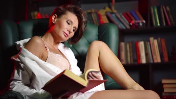 alluring middle aged woman is reading book in home biblioteca, sitting on luxury chair