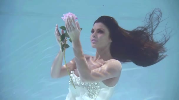 Porträt einer schönen Frau blickt auf eine schwimmende Blume unter Wasser, nimmt sie und riecht.