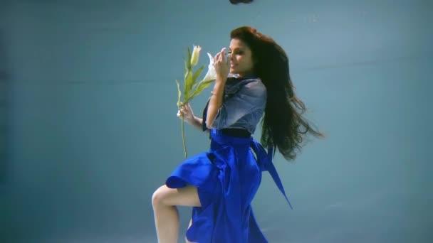okouzlující brunetka žena je oblečená v šaty a sako, drží lily, plovoucí pod vodou