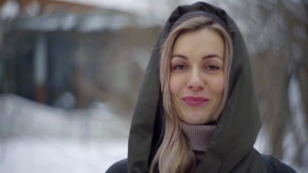 blonde Frau mit dunklen Augen und Klammern an den Zähnen lächelt breit im Freien im Wintertag