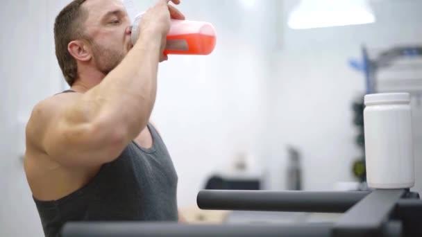 Kavkazská sportive člověk pije proteinový koktejl s džusem v tréninkové haly