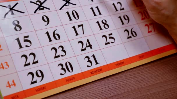 Close-up of mans hand making marks on a calendar.