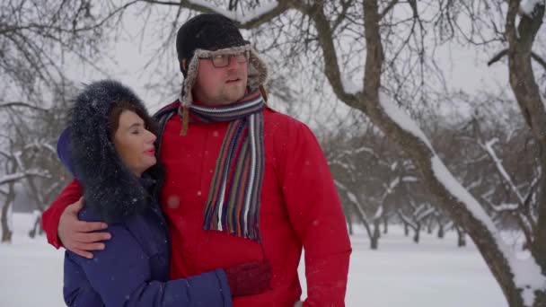 middle-aged couple walks through the Park during the winter in the snow. warm comfortable clothes. man with glasses talking to his wife
