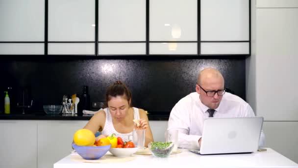 podnikatelská rodina má snídaně ráno doma v kuchyni a práci na počítači. pití mléka ráno