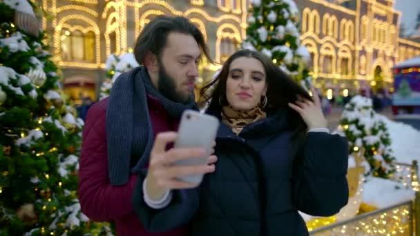 Édes szerető Internet rabja pár séta a téli üdülés a város és a képeket a szociális hálózatok a telefon