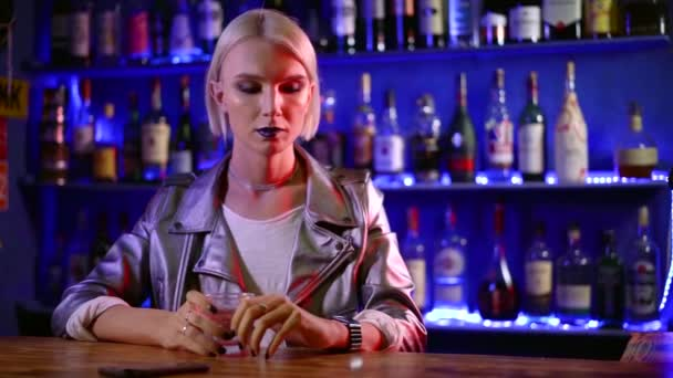 young androgynous woman is holding glass with alcohol beverage, sitting alone in a bar in night
