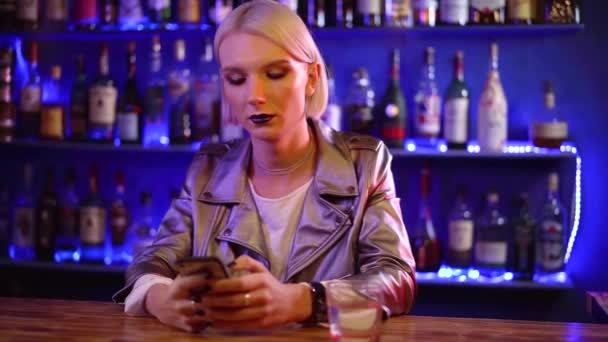 young transsexual man is dressed like a woman is typing sms by mobile phone sitting in a bar in nightclub alone
