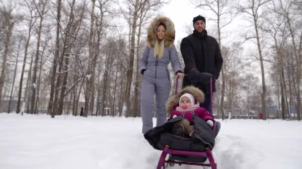 man and woman are strolling together in park in winter and carrying their little child
