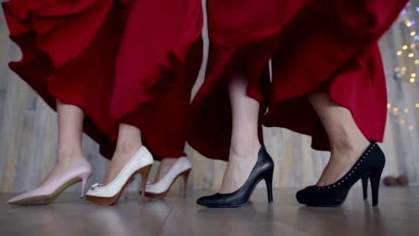 legs of four girls in high heels, red dresses develop