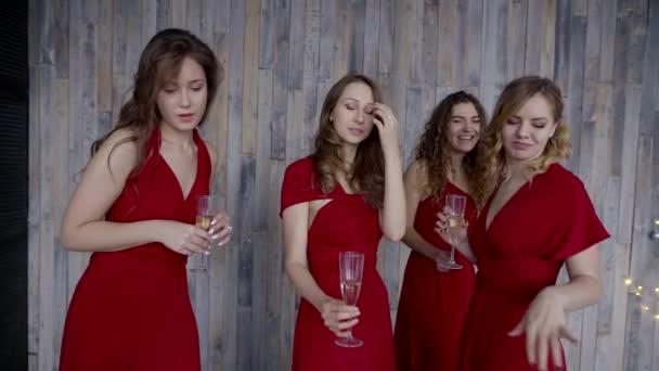 čtyři krásné dívky v téže červené šaty, baví se sklenkami vína
