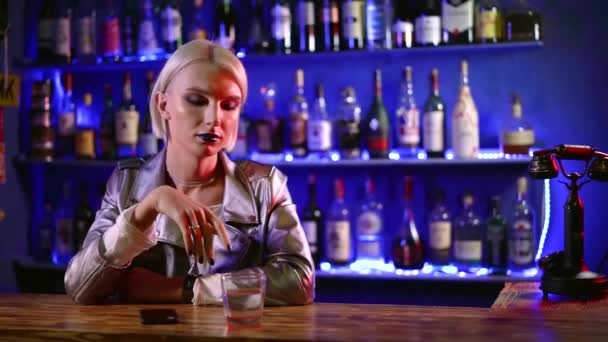 homosexual young man is looking like a woman is sitting in bar alone in evening, touching glass