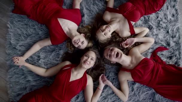 čtyři ženy vtipné jsou ležící na podlaze, drželi se za ruce, při pohledu na fotoaparát a vesele křičí