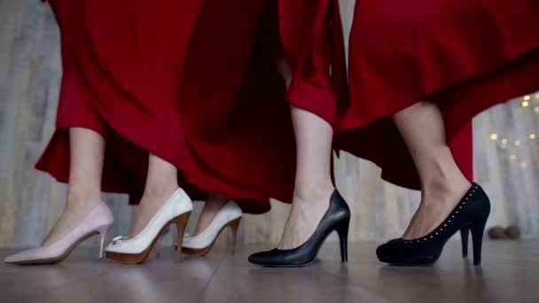 close-up view on feet of four young women are shod in white and black shoes, they are waving skirts