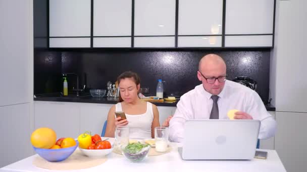 Husband and wife using gadgets during dinner and dont talk to each other.