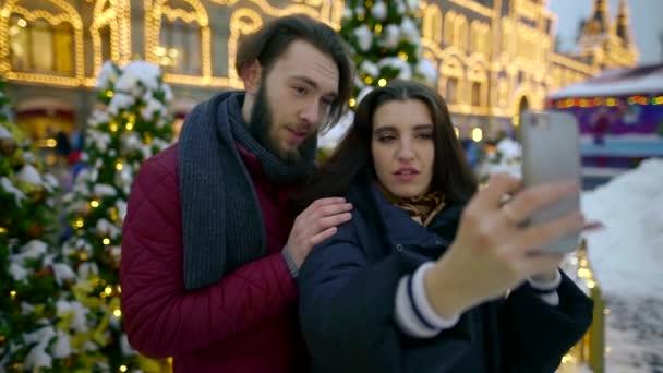 Emocionální a šťastný pár s pár selfie na smartphone proti krásné vánoční dekorace a stromy v parku.