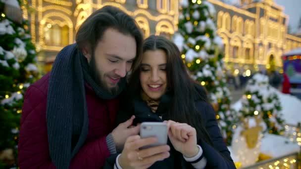 Közelről nézi a selfies egy okostelefon, hogy szabadtéri karácsonyi park gyönyörű pár portréja.