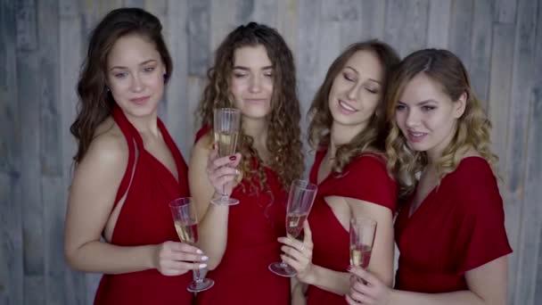 Négy csodálatos fiatal lány pózol a pezsgős poharak, pirítás, és mosolyogva,