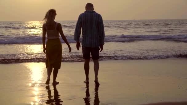 Nászút fiatal házaspár, séta a naplemente a tengerparton. napkitörés. Boldog romantikus newlywed pár élvezi az óceán naplemente alatt utazás ünnepek szabadság.