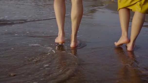 mužské a ženské nohy jsou krokování přes moře, vlny jsou mytí kroky a nohy, zadní Zobrazit detail