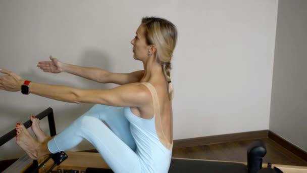 Pokoj wellness cvičení Pilates. Dívka instruktor vykazovat pohyb
