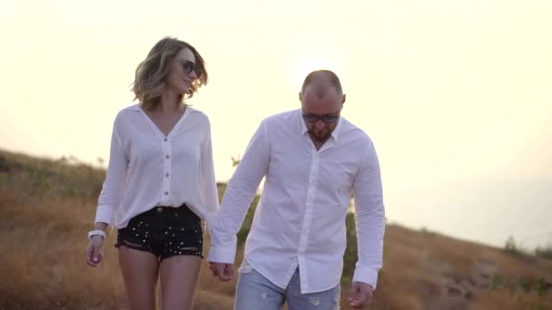 a woman and a man are on the mountain in white shirts by the handle, smiling, laughing, hugging.