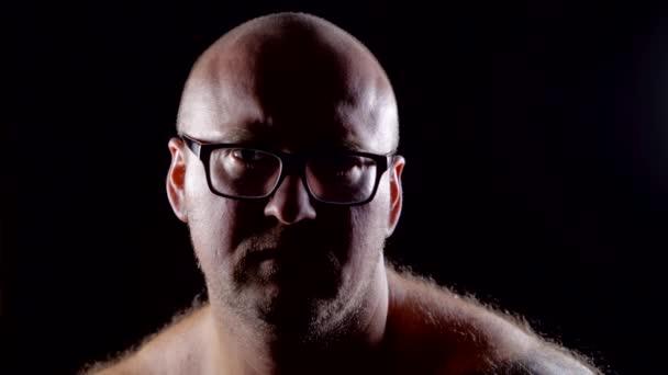 zlobí středního věku člověka je uvedení své brýle z tváře, se dívá na kameru, sedící v temné místnosti