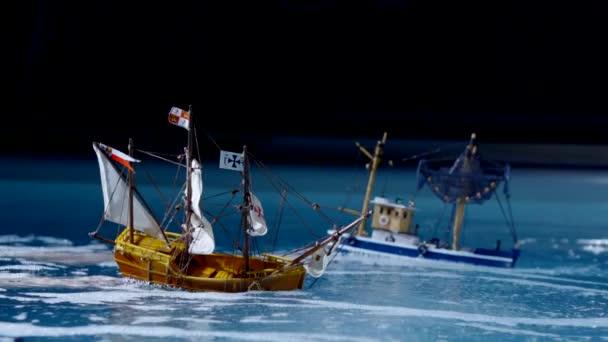dvě umělé lodě plující na vodě na tmavém pozadí, detail