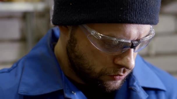 Porträt eines Mannes, der in einer metallverarbeitenden Werkstatt in Großaufnahme arbeitet.