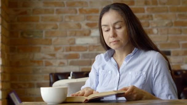 Felnőtt nő Olvasson egy könyvet a szobában. Aranyos lány tanul és irodalom leafing keresztül egy könyv, egy kávézóban kávét iszik oldalnyi olvasása