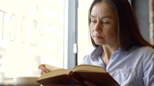 Egy felnőtt nő egy szobában, nagy könnyű ablak közelében egy könyvet olvas. Aranyos lány, tanulás és az olvasás, irodalom leafing keresztül a könyv lapjain