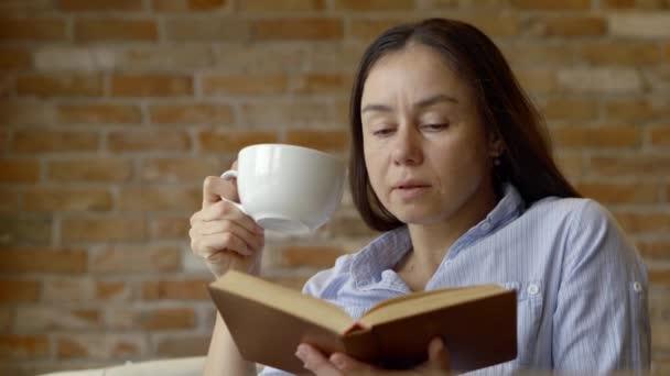 Egy felnőtt nő, olvasson egy könyvet egy kávézó, egy élénkítő cappuccino csésze. Aranyos lány, tanulás és az olvasás, irodalom leafing keresztül a könyv lapjain