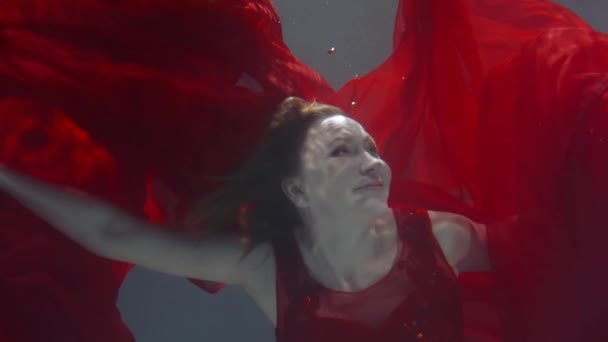 Charming woman on art fashion shooting in water, floating in stylish dress.