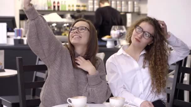 Két vidám és boldog lány szemüveg selfies vesz egy okostelefon, egy kávézó.