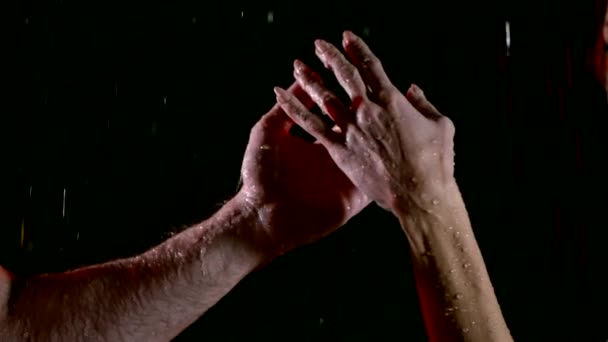 The hands of two lovers: big strong arm of a muscular man and small gentle of a woman under rain, studio shot against black background.